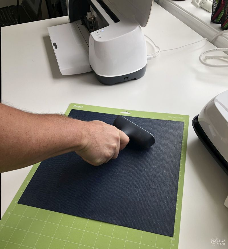 using a brayer to secure heat transfer vinyl to a cutting mat