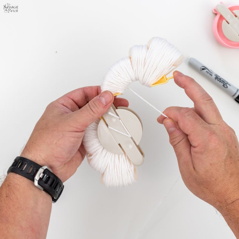 wrapping yarn around a pom pom maker to make diy ghosts