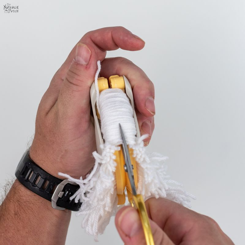 cutting yarn in a pom pom maker with scissors