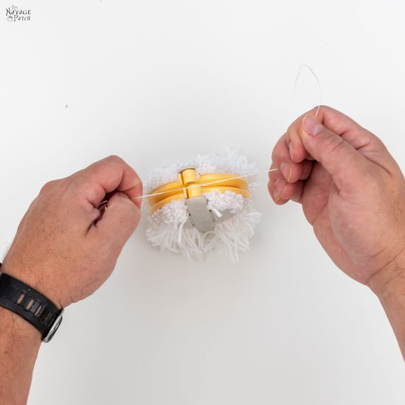 tying floss to a pom pom maker