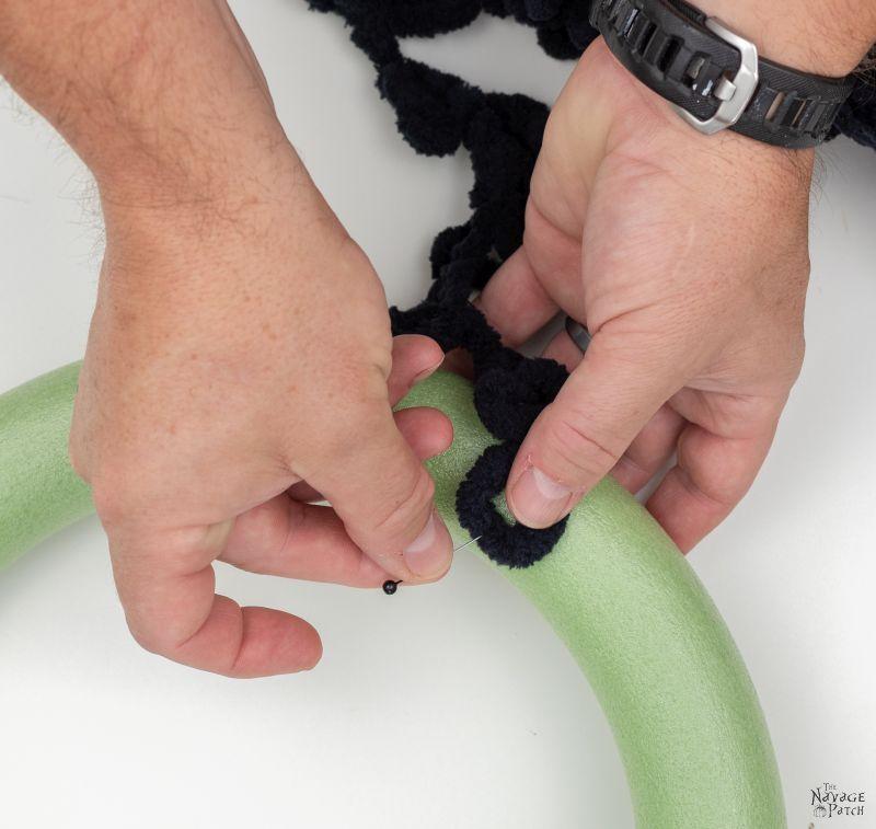 pinning loop yarn onto a wreath form to make a diy spider wreath