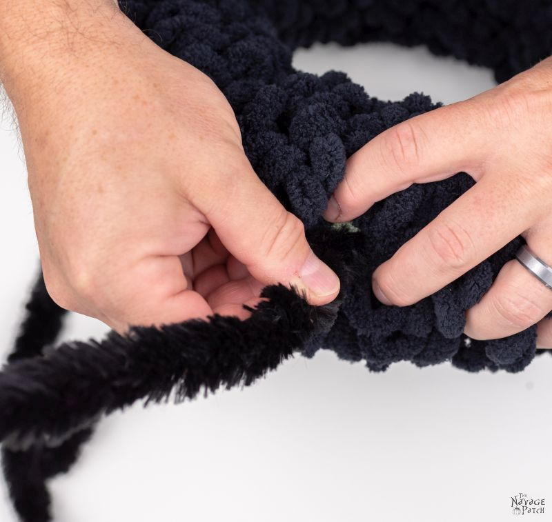 attaching chenille stems to a wreath form to make a spider wreath