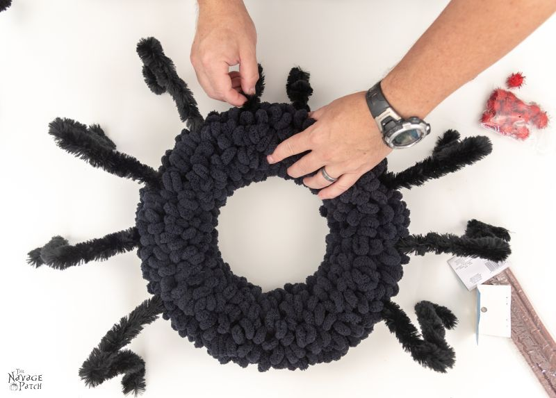 attaching chenille legs to a spider wreath