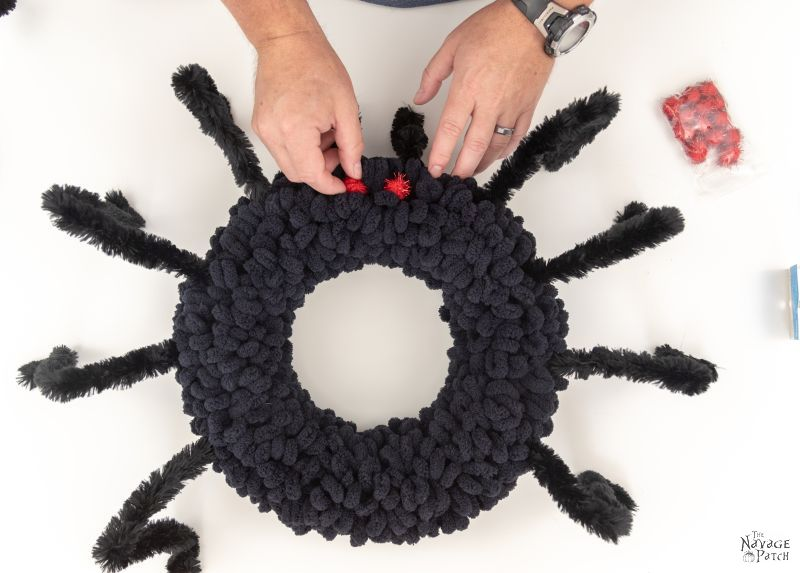 adding pom pom eyes to a spider wreath