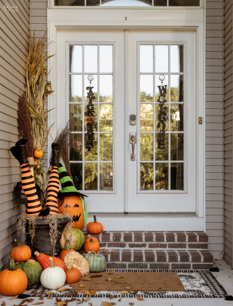 DIY Witch Legs in an urn surrounded by pumpkins on a front porch