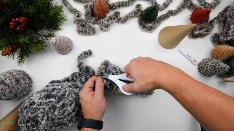 cutting yarn after making a faux fur tree on a craft cone