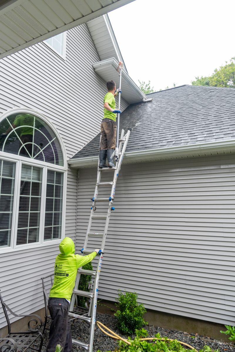 two men washing vinyl siding on a house