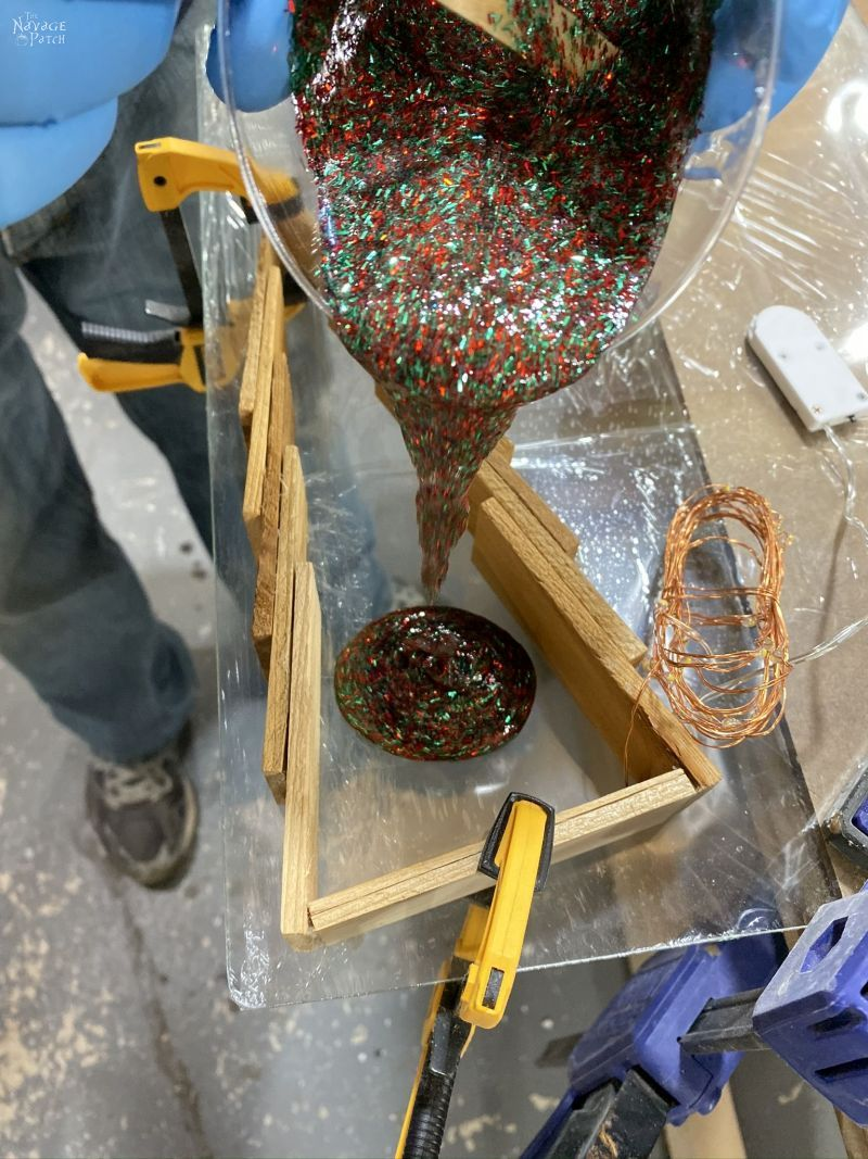 pouring red and green glitter epoxy into a wood shim tree
