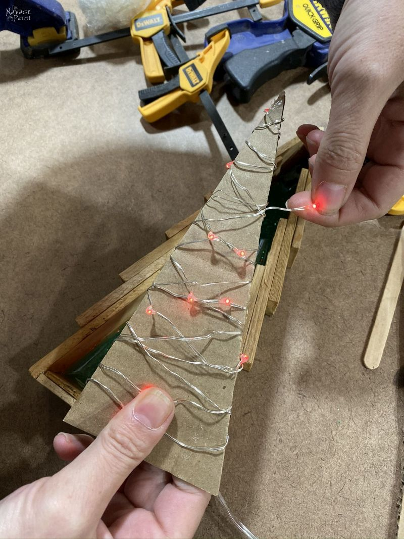 wrapping string lights around a cardboard triangle