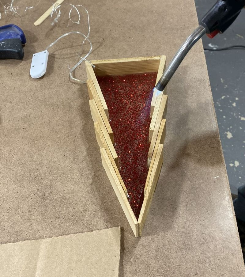 pouring red glitter epoxy into wood shim trees