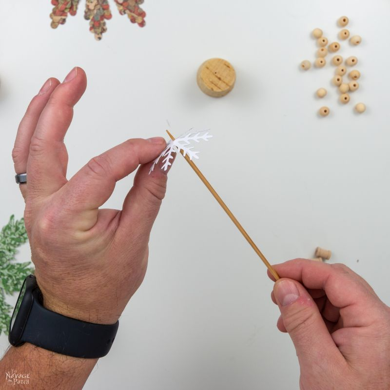piercing a paper snowflake with a bamboo skewer
