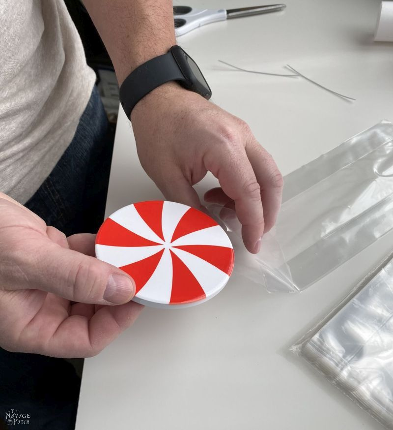putting a peppermint candy coaster into a treat bag