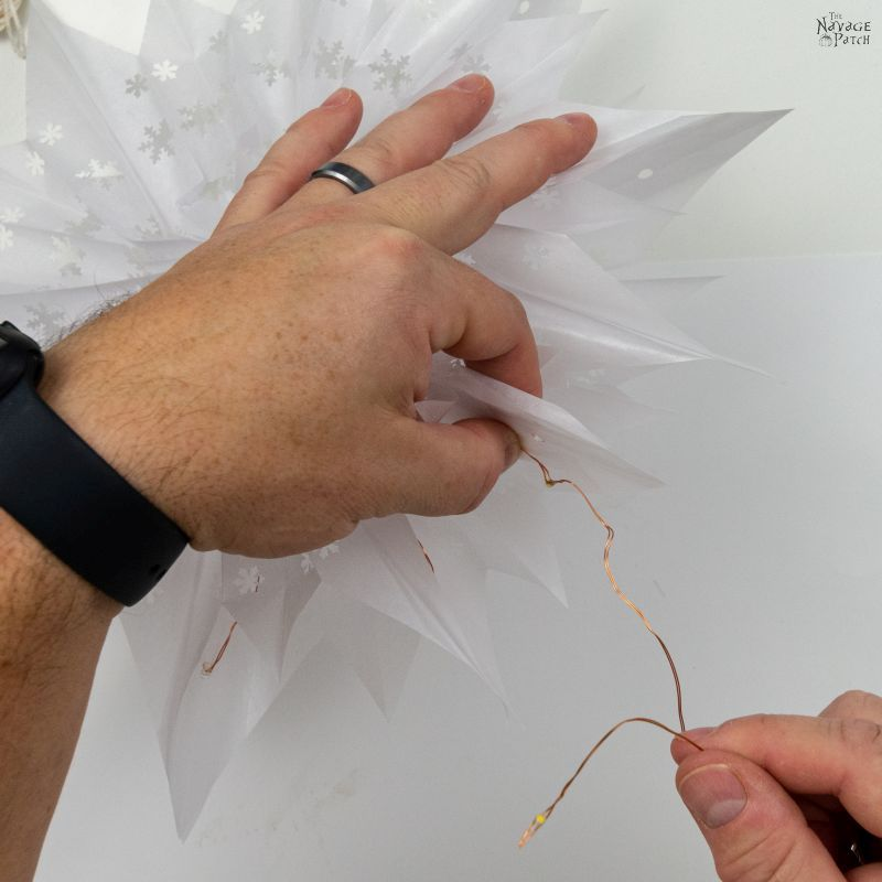 weaving fairy lights through a snowflake star