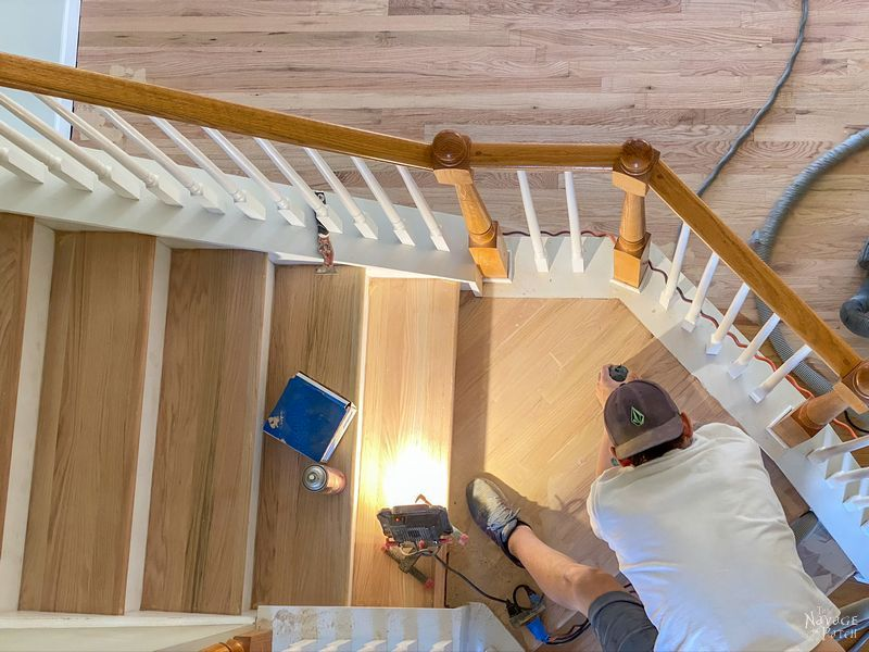 man sanding hardwood stairs with a random orbit sander