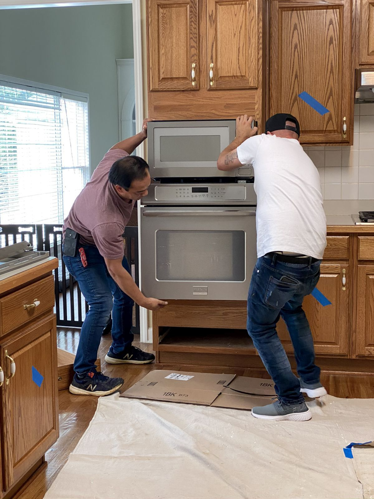 two men removing a wall oven