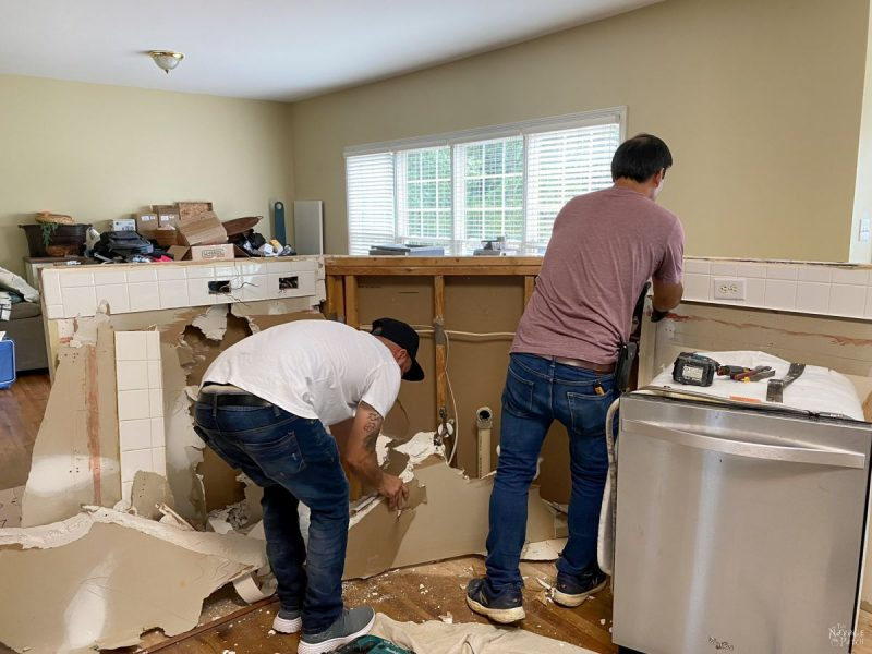 two men removing drywall from a kitchen island