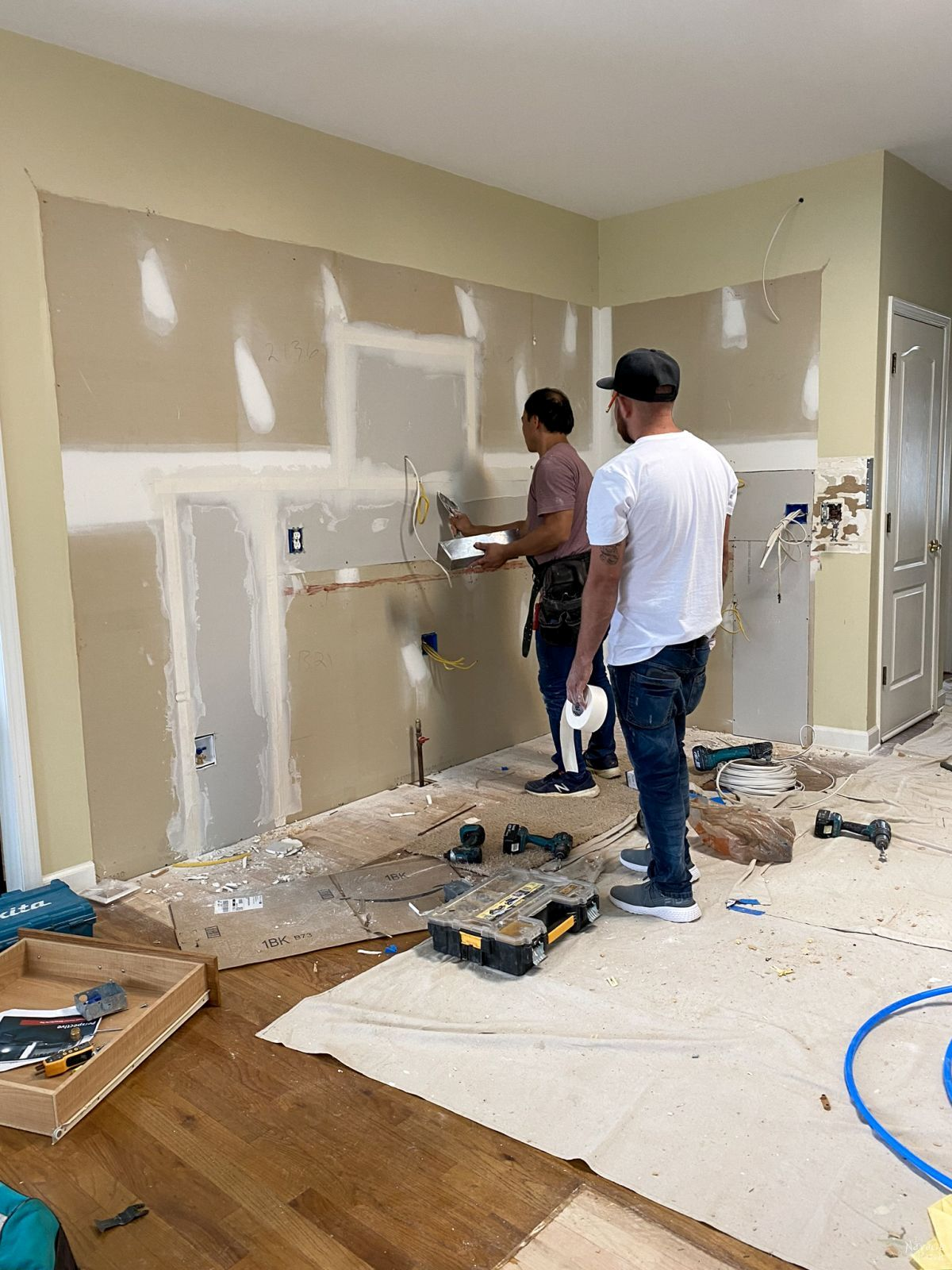 taping drywall in a demoed kitchen