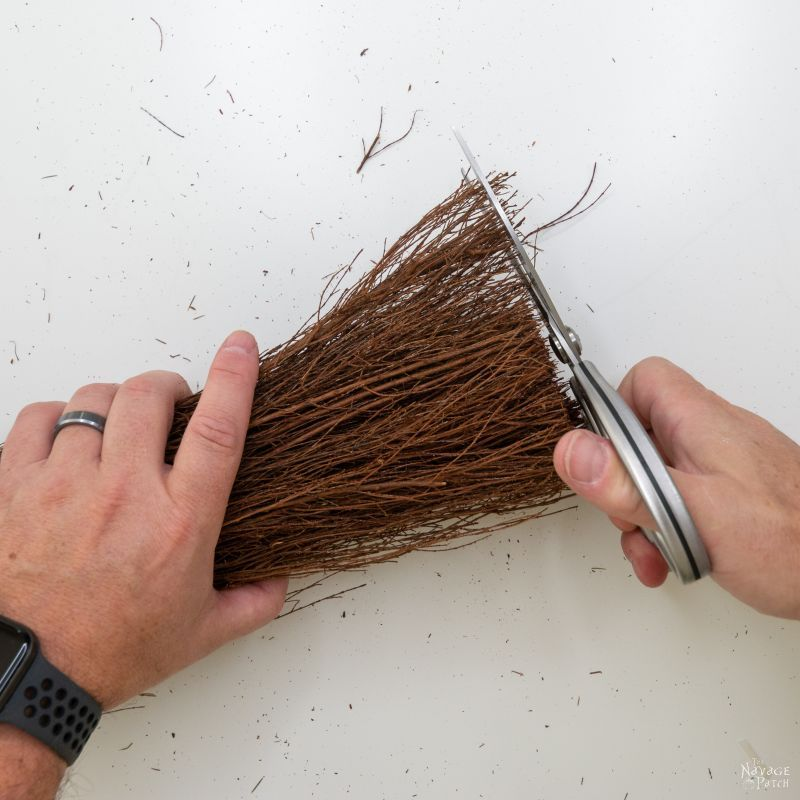 trimming the broom with scissors