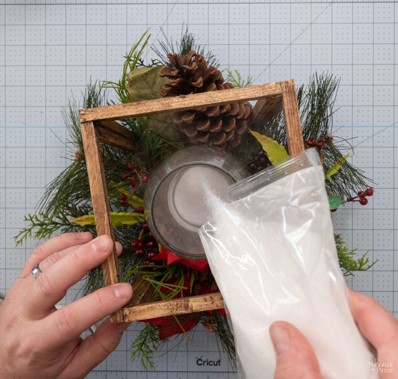 adding sand to a glass vase