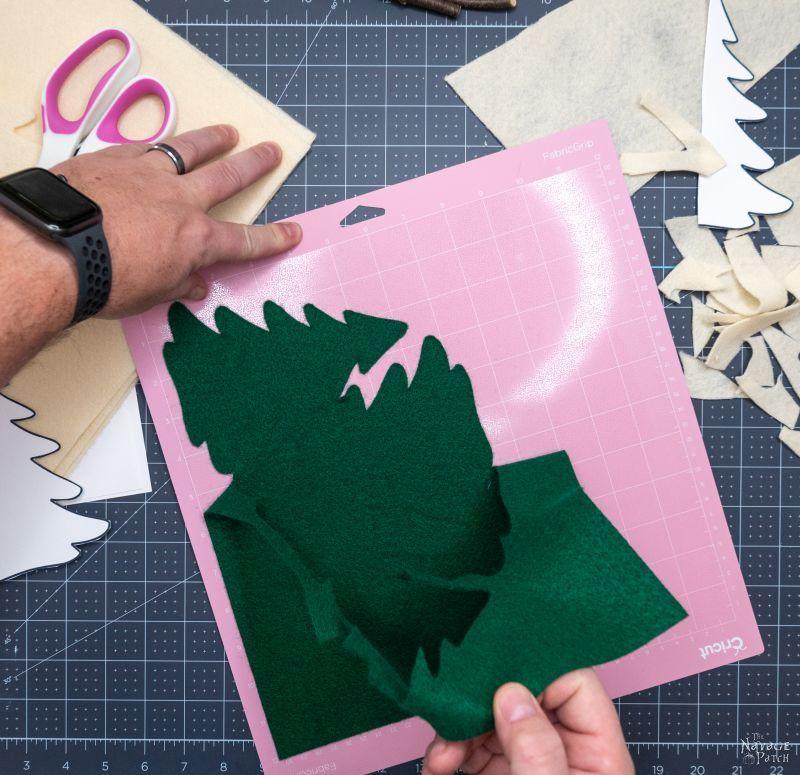 peeling green felt trees from cricut fabric mat