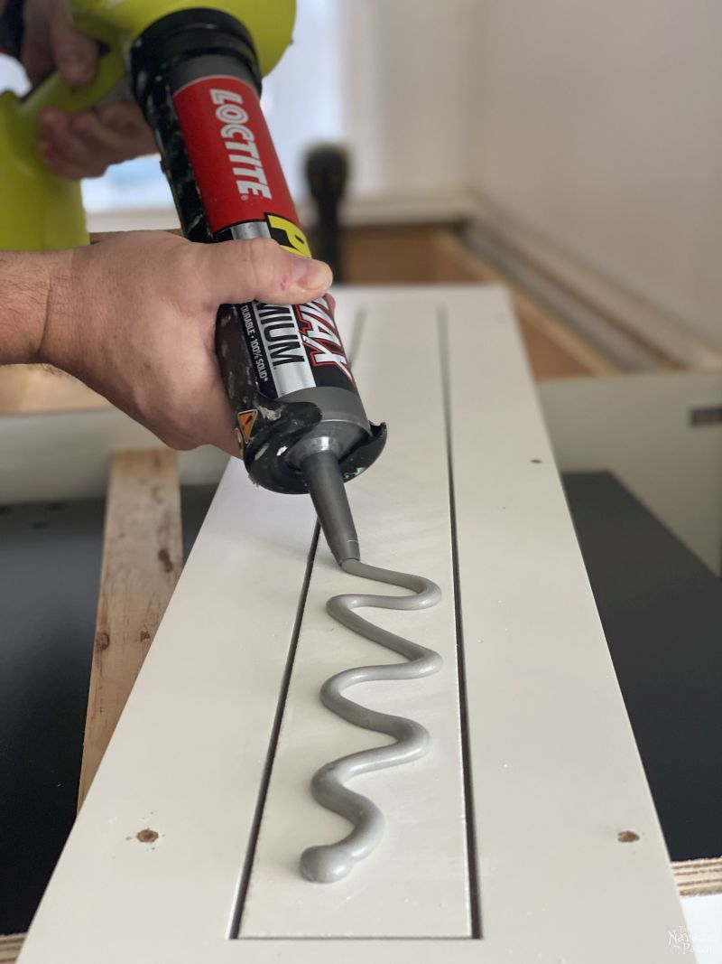 putting construction adhesive on a drawer face