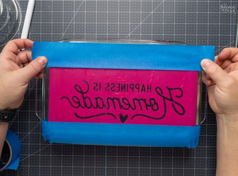 putting tape around a stencil on a baking dish