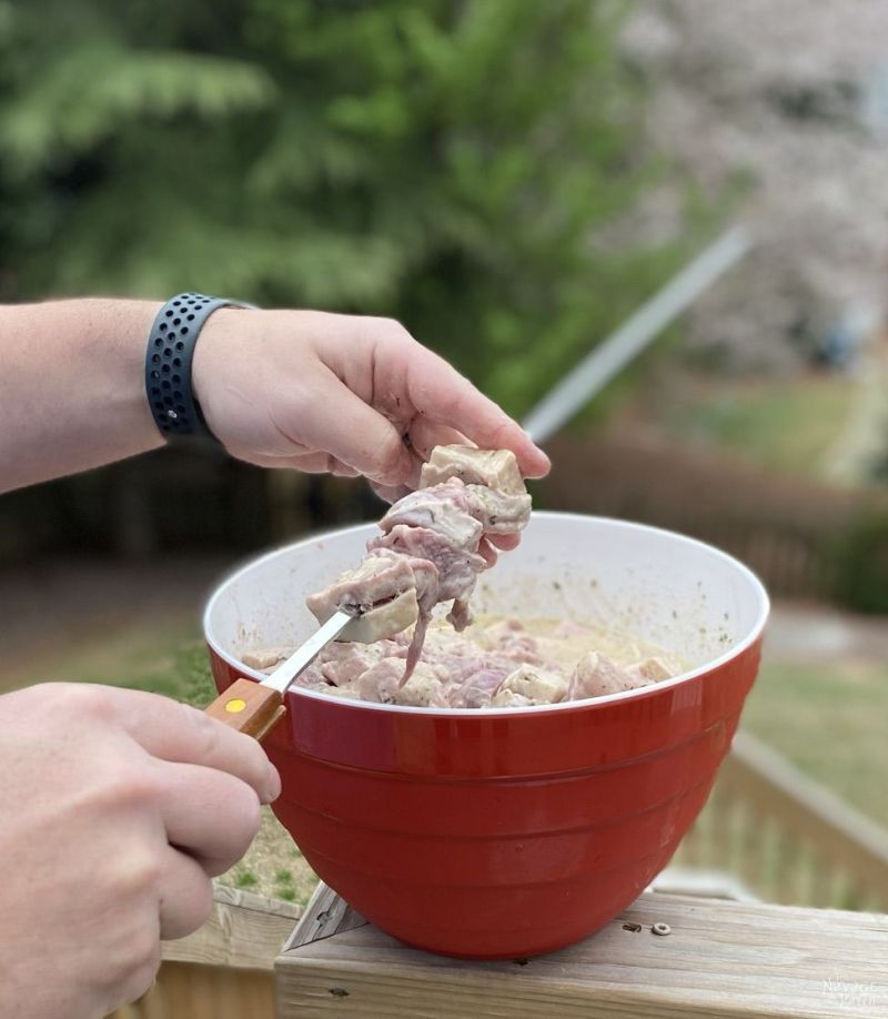 putting lamb on a skewer
