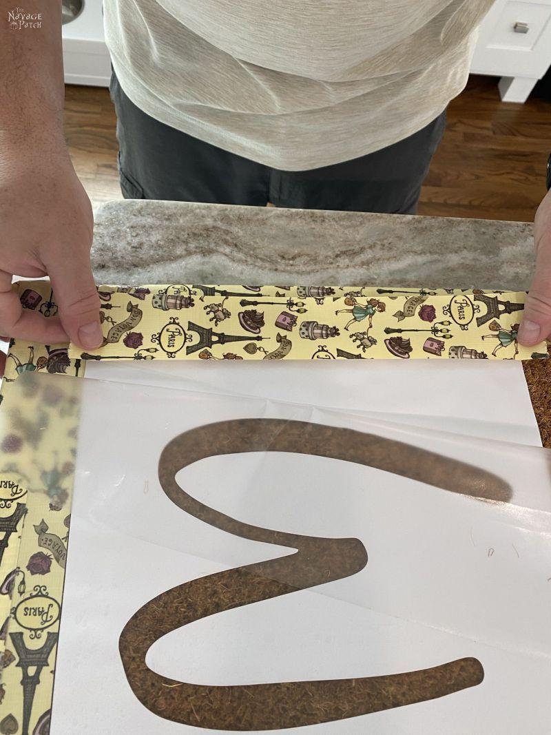 placing a stencil on a door mat