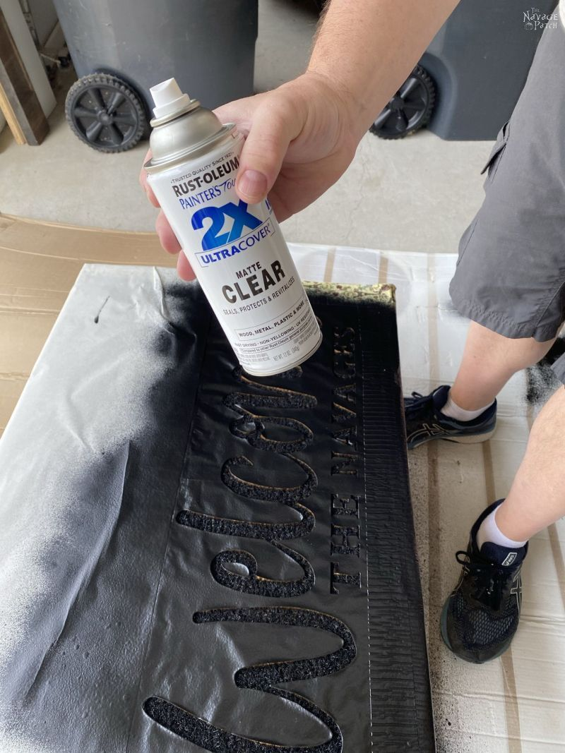 spraying a personalized door mat with sealant