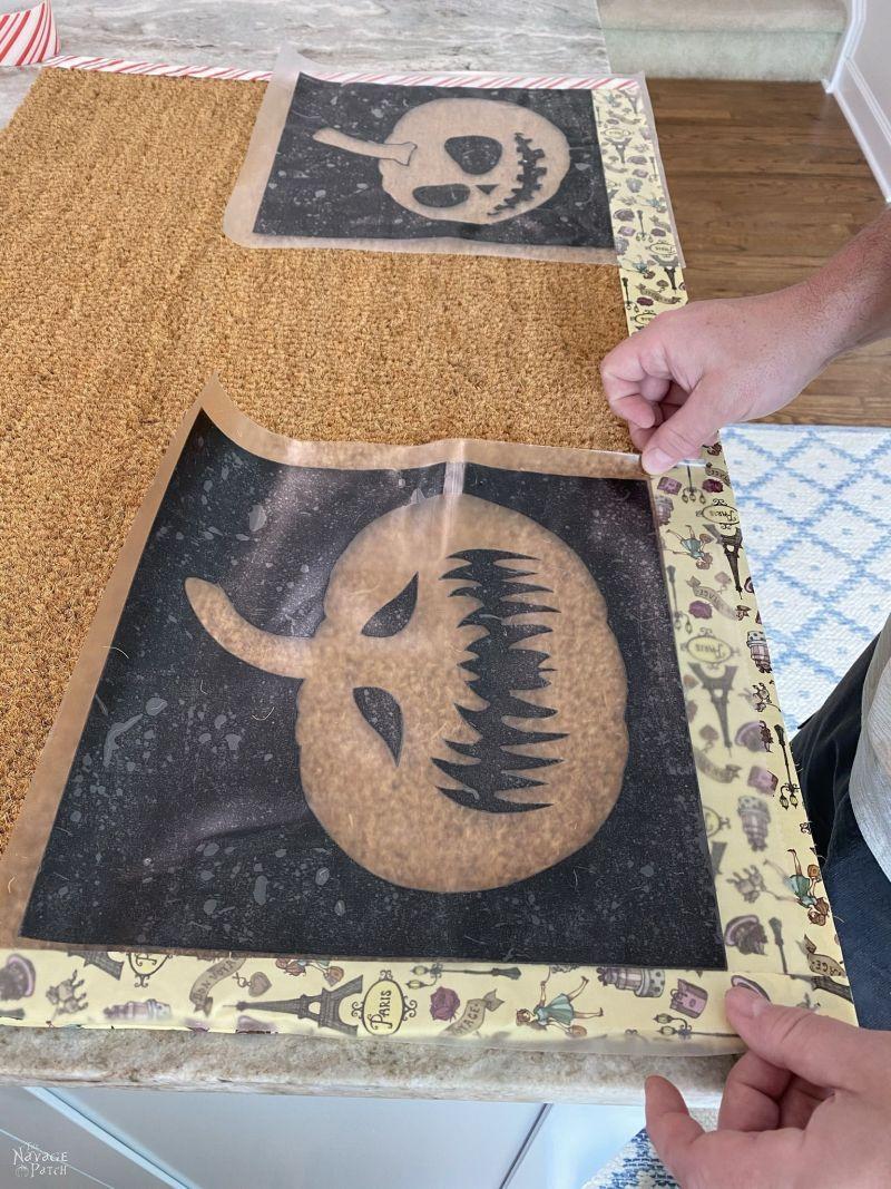 putting pumpkin stencils on a doormat