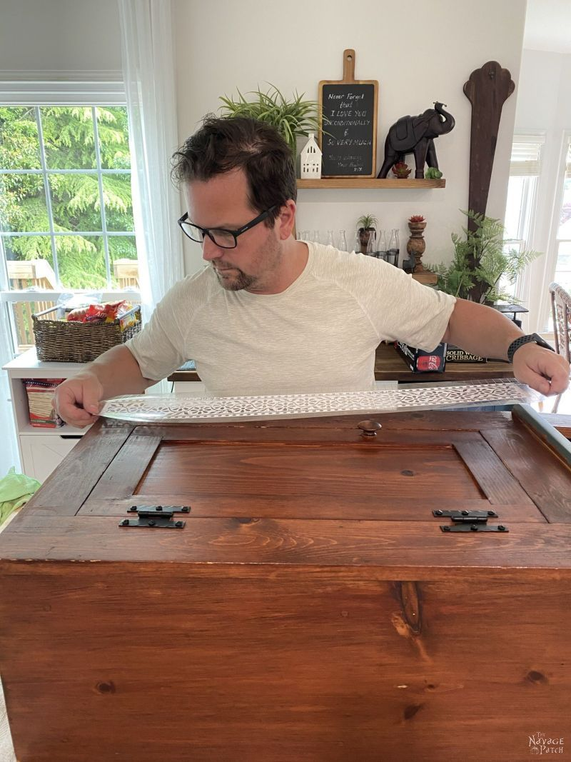applying stencil vinyl to a cabinet