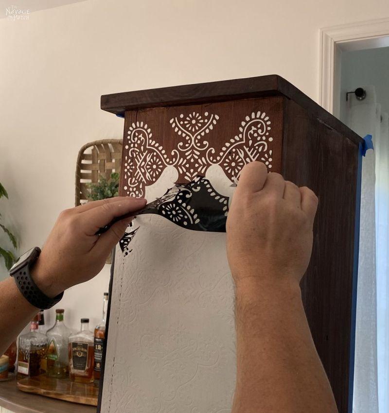 peeling stencil vinyl from a cabinet