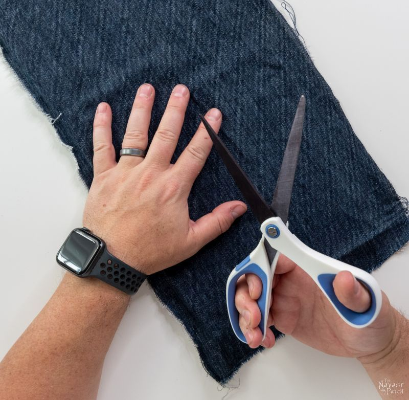 cutting blue jeans with scissors