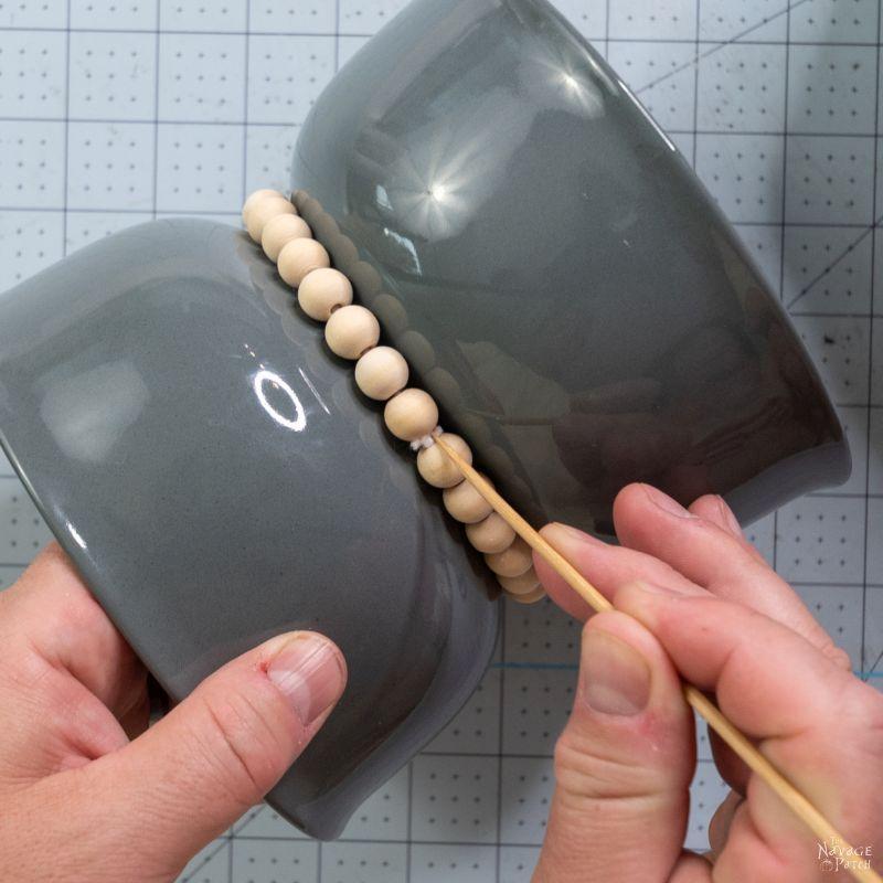tying beads around a bowl