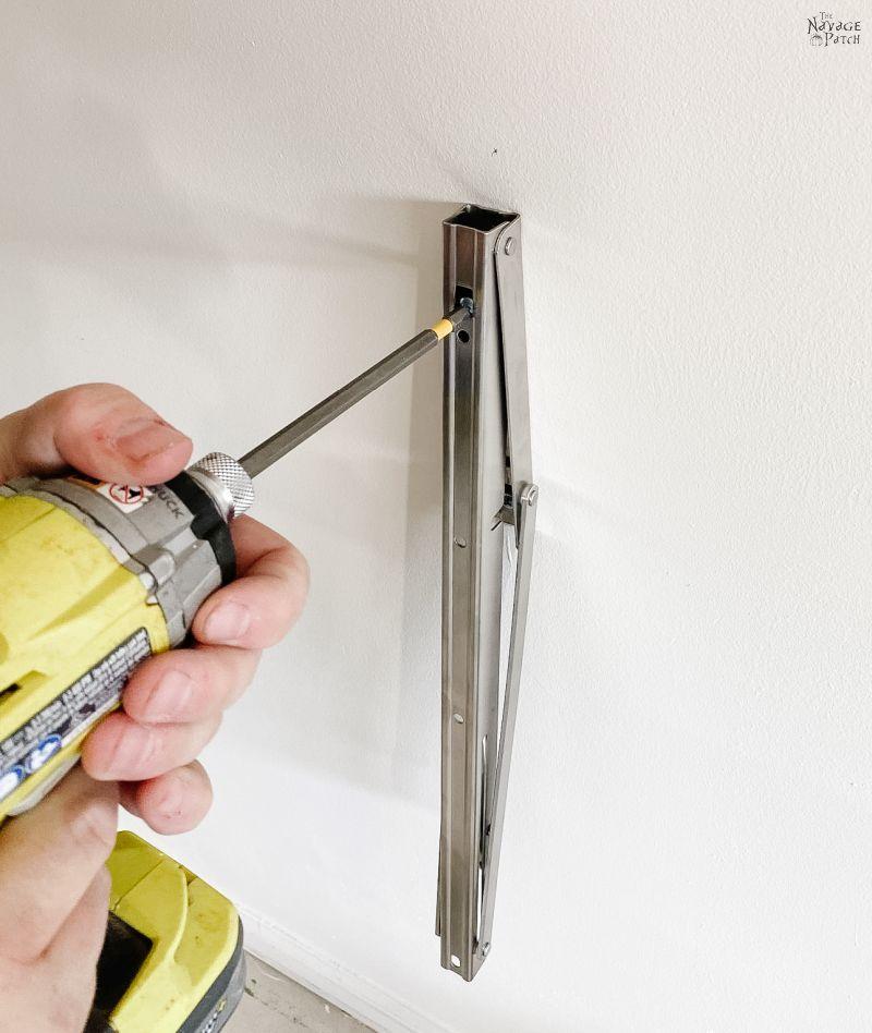 homem instalando um suporte dobrável em uma parede de garagem