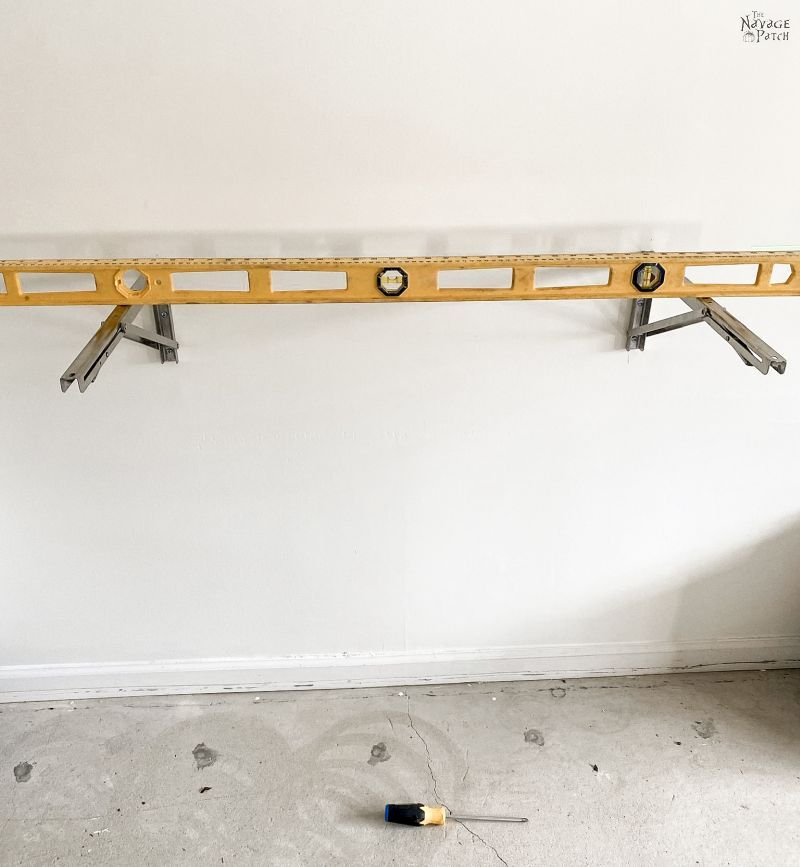 nível de feixe i colocado em dois suportes dobráveis montados em uma parede
