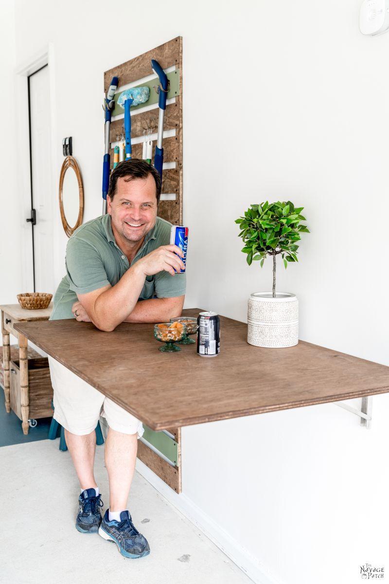 homem encostado em uma mesa dobrável em uma garagem bebendo cerveja