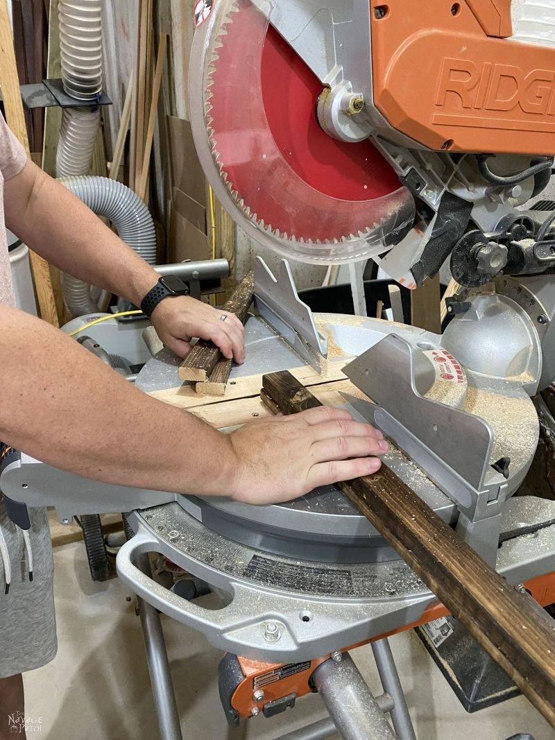 man cutting two stained furring strips with a circular saw