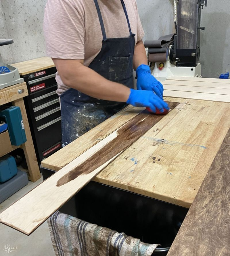 man staining a plywood slat that will be used to make a mop and broom storage rack