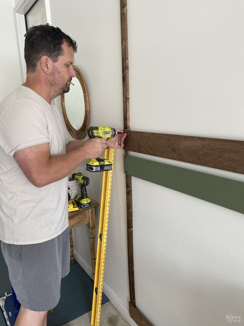 screwing slats onto a wood frame on a wall