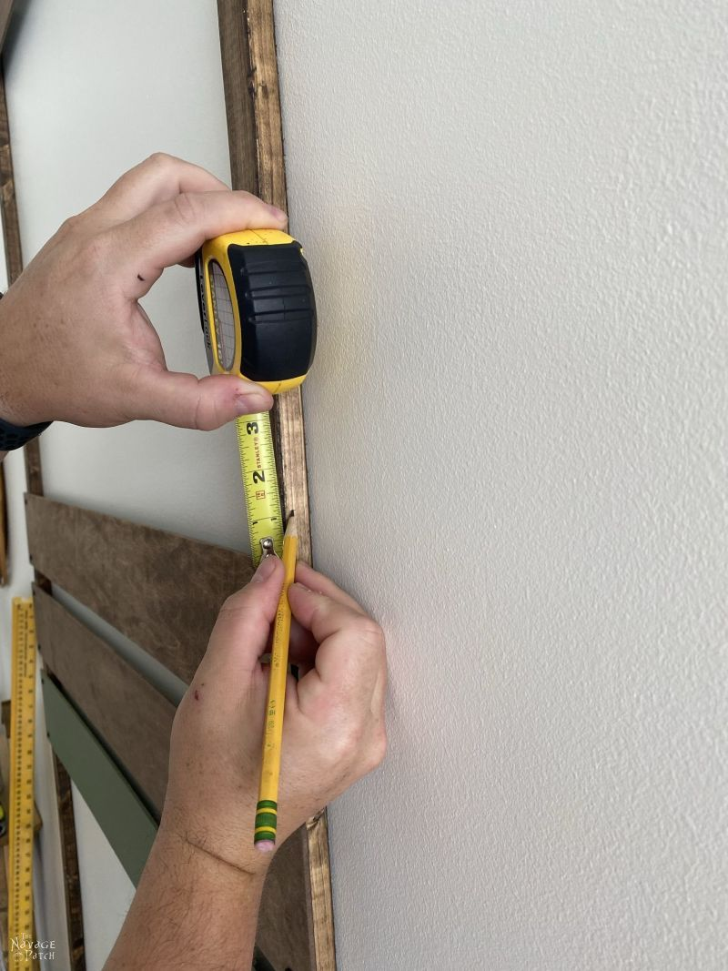 man marking with pencil where he will install a wood slat to a frame on the wall