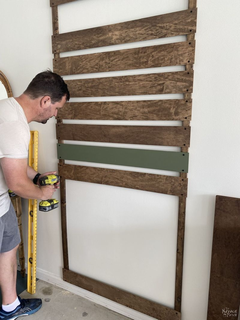 man installing wood slats to build a mop and broom storage rack