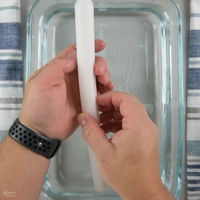 man's hands holding a white candle over a baking dish filled with warm water