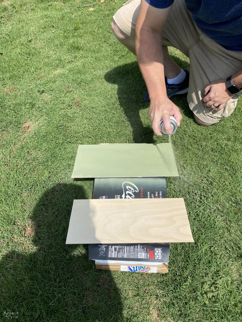 man spraying two thin boards with green spray paint