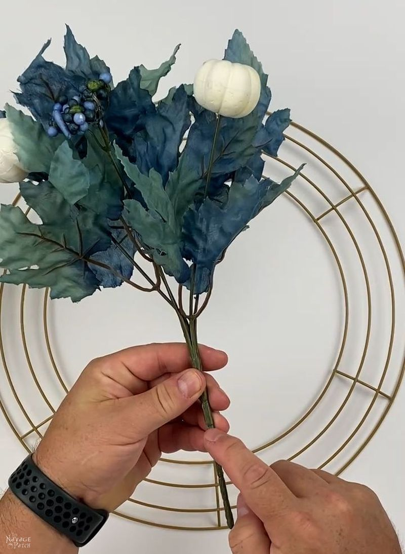 man holding a dollar tree floral pick