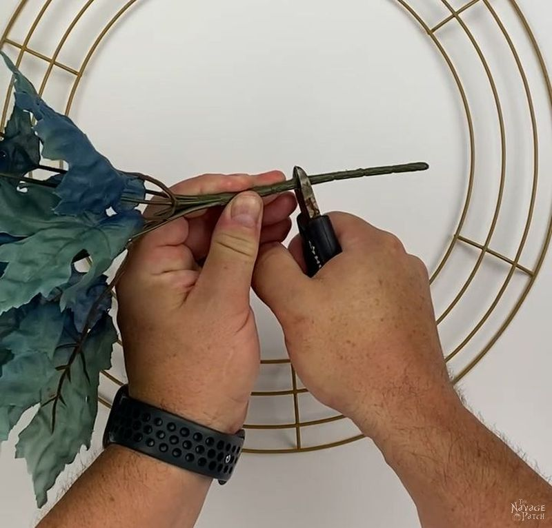 man cutting the stem of a dollar tree floral pick