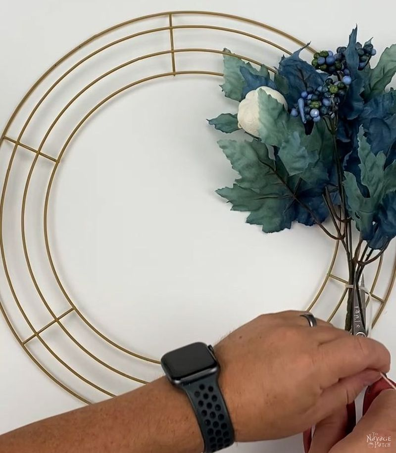 man attaching a floral pick to a wreath form