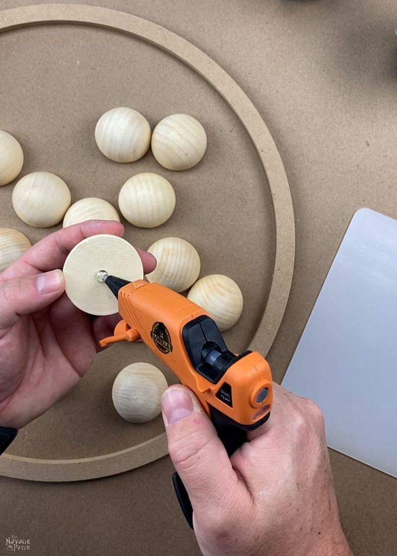man putting a dab of hot glue on a split wood ball
