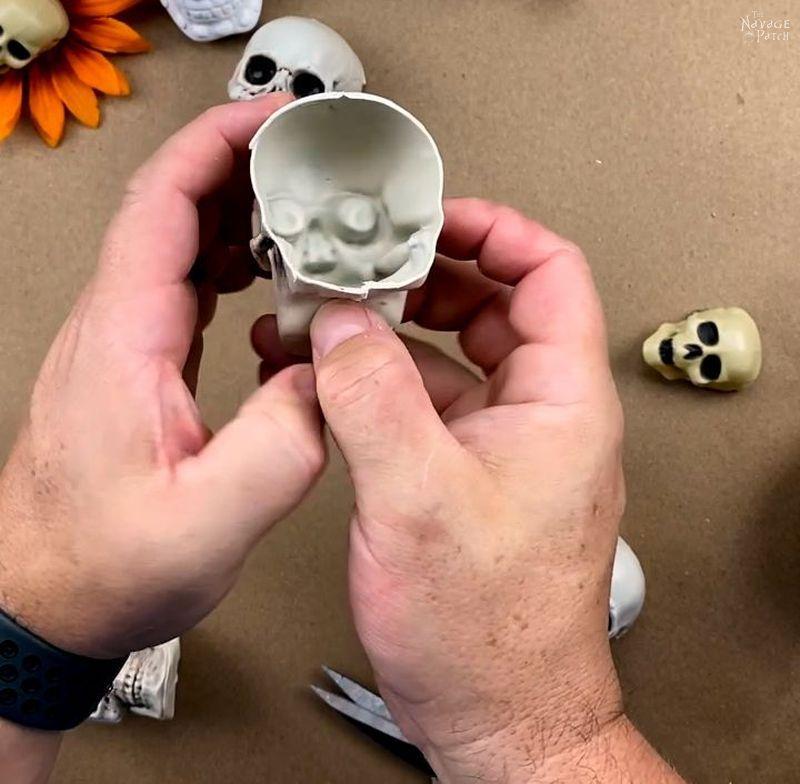 man cutting a plastic skull with scissors