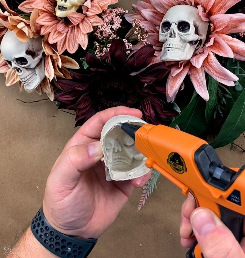 man putting hot glue on a plastic skull